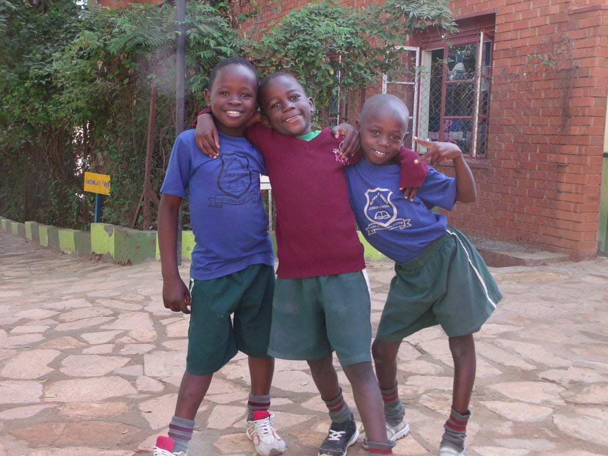 Close up picture of 3 kids from computer outreach program in Ethiopia