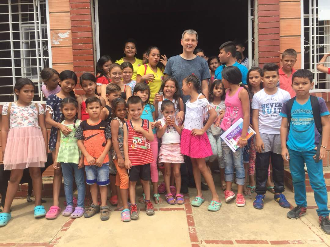 Dr. Aleksey with kids in group picture in Venezuela
